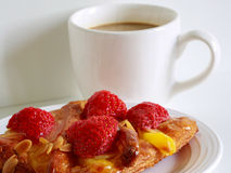 A delicious Strawberry Danish pastry and a white cup of coffee on white background Royalty Free Stock Photos