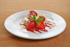 Delicious strawberry dessert. With sliced fresh strawberries drizzled with fruity syrup and garnished with mint served on a plain white plate stock photos