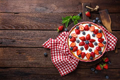 Delicious strawberry pie with fresh blueberry and whipped cream on wooden rustic table, cheesecake Stock Image
