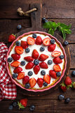 Delicious strawberry pie with fresh blueberry and whipped cream on wooden rustic table, cheesecake Stock Photo