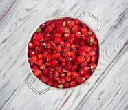 A delicious strawberry. Ripe berries. We collect strawberries. Berries, blurred wooden background stock image