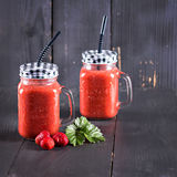 Delicious Strawberry Smoothie. Healthy strawberry smoothie in a mason a jar glass with scattered berries over a rustic wood background. healthy food for Royalty Free Stock Image