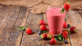 Strawberry smoothie. Delicious strawberry smoothie on wood Royalty Free Stock Photo