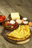 Delicious stuffed omelette on a wooden board. Fried egg omelette with cherry tomatoes, garlic and chili peppers. Nutritious breakf Stock Photos
