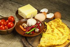Delicious stuffed omelette on a wooden board. Fried egg omelette with cherry tomatoes, garlic and chili peppers. Nutritious breakf Stock Photo