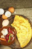 Delicious stuffed omelette on a wooden board. Fried egg omelette with cherry tomatoes, garlic and chili peppers. Nutritious breakf Royalty Free Stock Photography