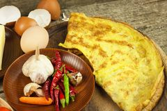 Delicious stuffed omelette on a wooden board. Fried egg omelette with cherry tomatoes, garlic and chili peppers. Nutritious breakf Royalty Free Stock Photos