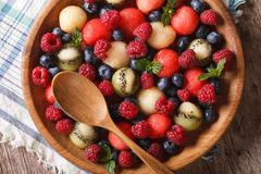Delicious summer fruit salad in bowl closeup. horizontal top vie Stock Photos