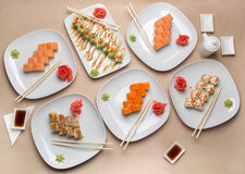 Delicious sushi on different plates on the table Royalty Free Stock Photos