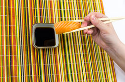 A delicious sushi rice and a slice of salmon, holding bamboo sticks in his hand, is lowered into a bowl with soy sauce on a multic royalty free stock photography