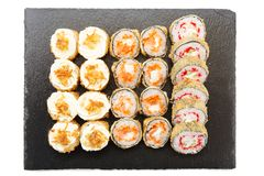 Delicious sushi rolls, nigiri and salmon sushi rolls. Sushi isolated on shale food board on white background royalty free stock images