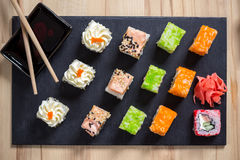 Delicious sushi rolls served on black board with chopsticks Stock Photo