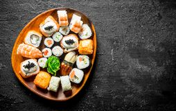 Delicious sushi rolls with shrimp, vegetables and salmon on a wooden plate. On black rustic background stock photography