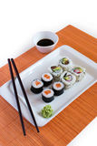 Delicious sushi rolls on white plate with chopsticks Stock Images