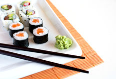 Delicious sushi rolls on white plate with chopsticks Royalty Free Stock Images