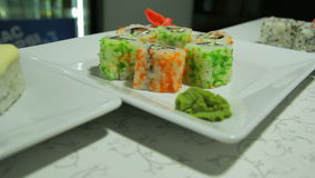 Delicious sushi rolls on white plate with wasabi and ginger stock video footage