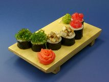 Delicious sushi rolls on wooden plate Royalty Free Stock Photos