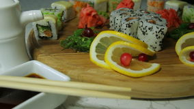 Delicious sushi rolls on wooden plate with wasabi and ginger stock footage