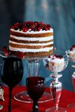 Delicious sweet buffet with berry cake and glasses with champagne on red table Stock Photo
