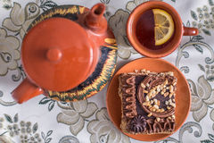 Delicious and sweet chocolate cake with cream and nuts and a сup of black tea with lemon. tea set with teapot, saucer and сup Royalty Free Stock Images