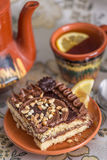 Delicious and sweet chocolate cake with cream and nuts and a сup of black tea with lemon. tea set with teapot, saucer and сup Stock Photos