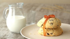 Delicious sweet chocolate-chips cookies with an orange ribbon. Milk-jug, on wooden table. Looped. stock footage