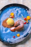Delicious sweet chocolate fondant with fruit served on blue plate, product photography for restaurant or patisserie royalty free stock photo
