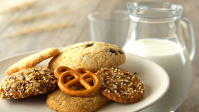 Delicious sweet cookies. Milk-jug and glass, on wooden rustic table. Looped. stock video
