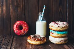 Delicious sweet covered colored donut glaze and a bottle of milk. A group of delicious sweet covered colored donut glaze and a bottle of milk on a dark wooden stock photo