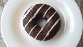 Delicious sweet donut with chocolate icing rotating on a plate. Rustic wooden table. Looped. stock video footage