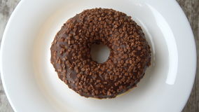 Delicious sweet donut with chocolate icing rotating on a plate. Rustic wooden table. Looped. stock video