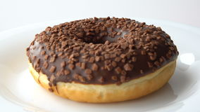 Delicious sweet donut with chocolate icing rotating on a plate. White background. Looped. stock video