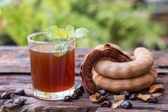 Delicious sweet drink tamarind. Tamarind juice - Delicious sweet drink tamarind, ripe tamarinds and seeds with mint leaves on rustic wooden table. Selective Stock Photos