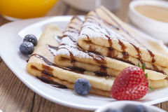 Delicious sweet French pancakes on a plate with fresh fruits Royalty Free Stock Image