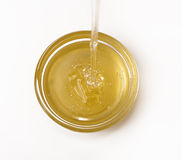 Delicious sweet honey flowing down in small glass bowl. Royalty Free Stock Photo