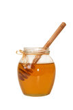 Delicious sweet honey in glass jar isolated on white background. Delicious sweet honey in glass jar. Honey and dipper in jar isolated on white background Stock Images