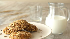 Delicious sweet oatmeal cookies with seeds. Milk-jug and glass, on wooden rustic table. Looped. stock footage