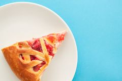 Delicious sweet pie on a plate on a blue background.Top view. stock photos