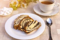 Delicious sweet poppy seed cake on a plate, on a table and a Cup of tea. stock image