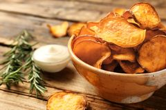 Delicious sweet potato chips in bowl, rosemary and sauce on table. Space for text royalty free stock images