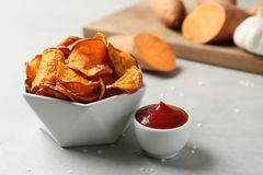 Delicious sweet potato chips in bowl and sauce. On table royalty free stock image
