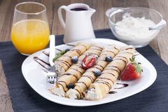 Delicious sweet rolled pancakes on a plate with fresh fruits Stock Images