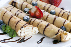 Delicious sweet rolled pancakes on a plate with fresh fruits Stock Photography