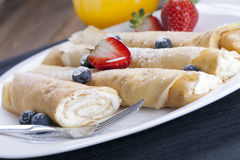 Delicious sweet rolled pancakes on a plate with fresh fruits Royalty Free Stock Photos