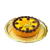 Delicious sweet round fruit cake with peaches, oranges, kiwi, grapes. On a round metal tray Stock Photos