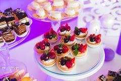 Delicious sweets on wedding candy buffet with desserts, cupcakes Royalty Free Stock Images
