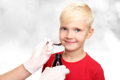 A delicious syrup, the boy drink a cure for the common cold. Stock Photos