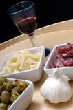 Delicious tapas and red wine. Italian tapas like cheese olives sausage garlic and red wine on a wooden plate royalty free stock image