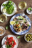 Delicious tapas - sandwiches sardines, mussels, octopus, grape, olives, tomato,avocado and white wine on wooden table, top view. Stock Photos
