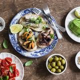 Delicious tapas - sandwiches with sardines, mussels, octopus, grape, tomato and avocado on wooden table royalty free stock photo